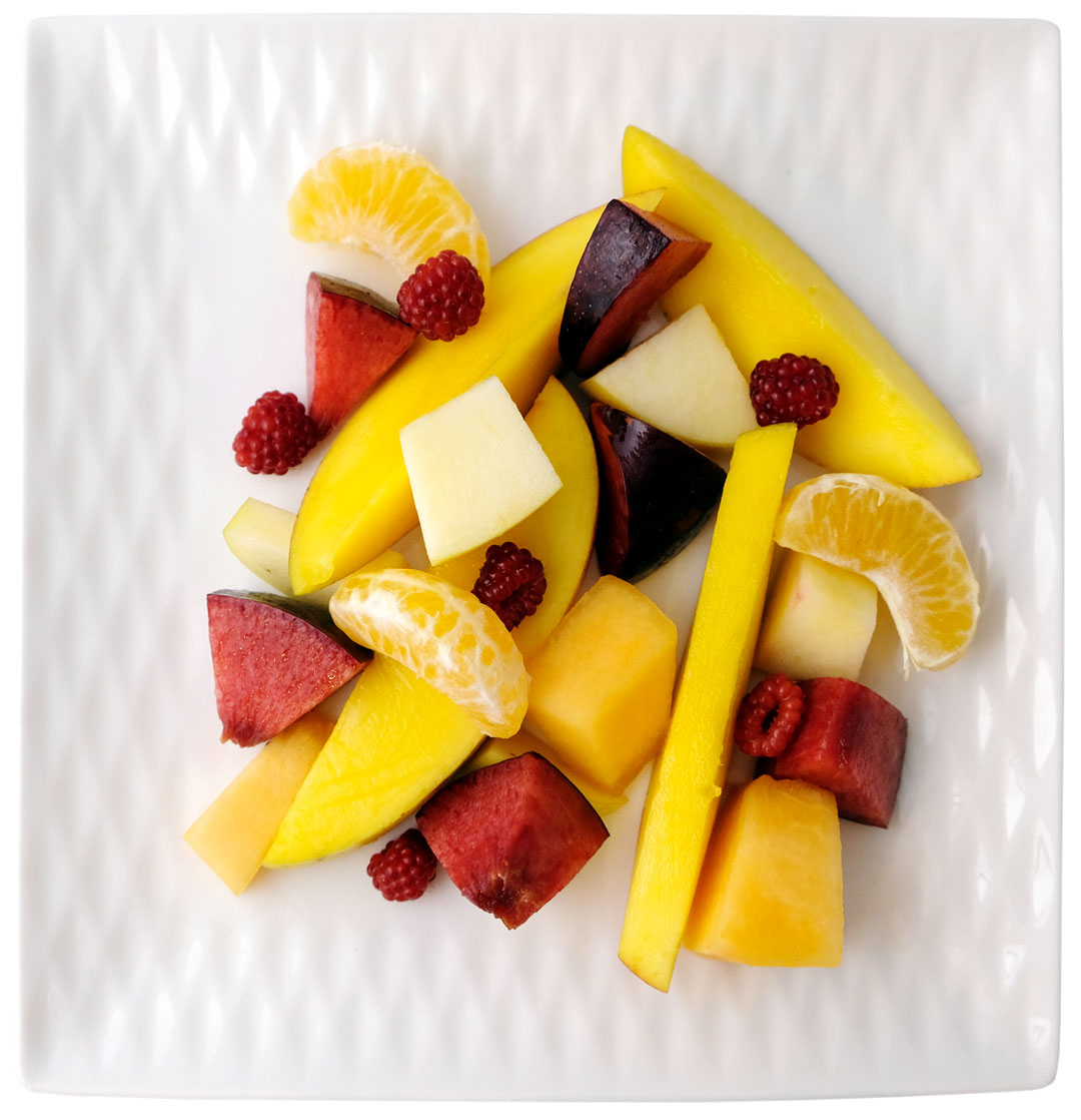 Disease prevention through a healthy diet. A plate of cut fruit consisting of mango, raspberry, mandarin, apple, cantaloupe and plum prepared by Eat Fresh Chef Inc.